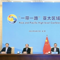 Chinese Foreign Minister Wang Yi (center) attends an online conference on Belt and Road cooperation in the Asia-Pacific in Beijing in June. | XINHUA NEWS AGENCY / VIA KYODO