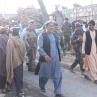 Nangarhar provincial official Ajmal Omar (in blue) walks with soldiers government of former President Ashraf Ghani.  | VIA REUTERS