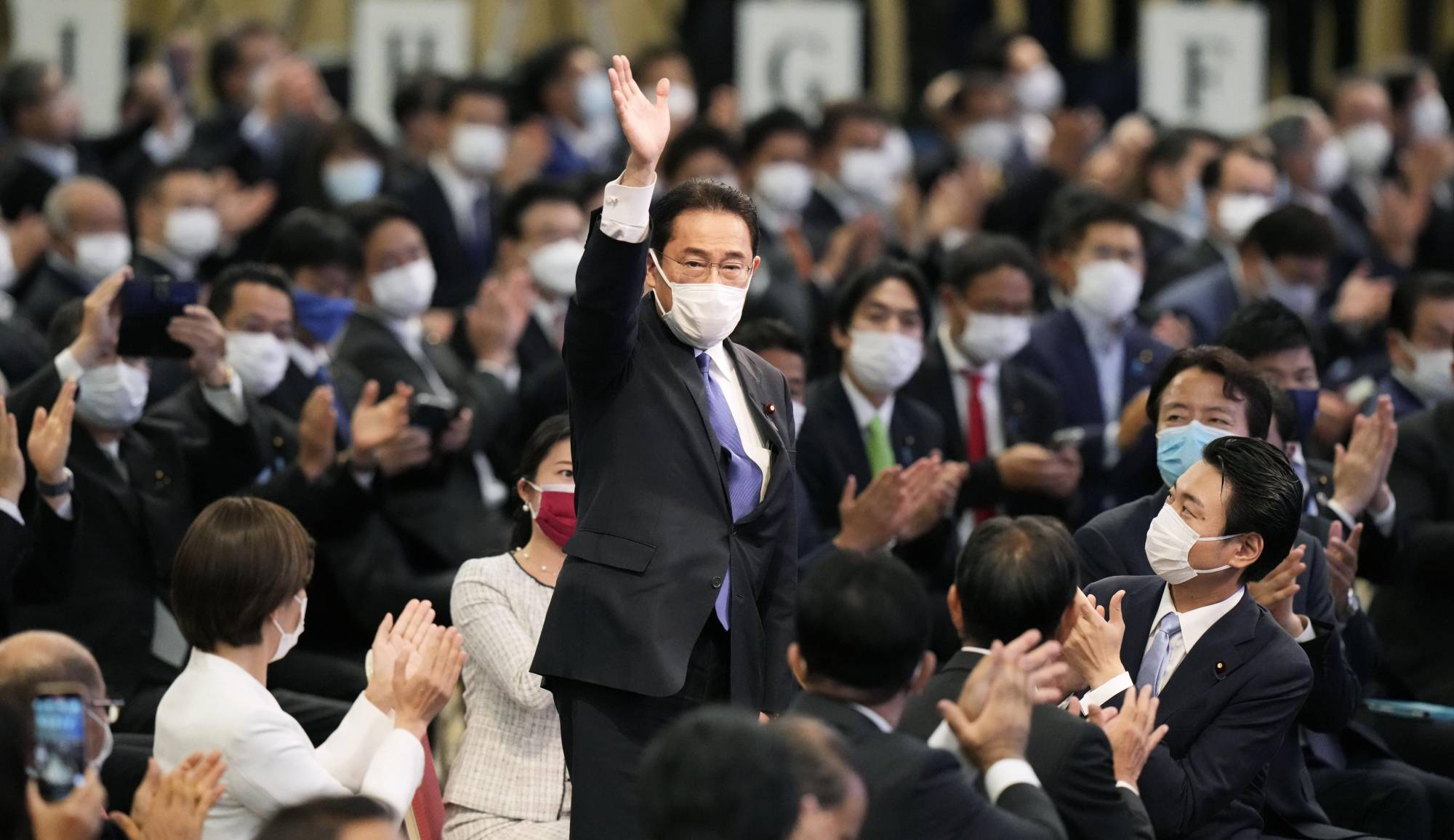 Former Foreign Minister Fumio Kishida waves after he was elected Liberal Democratic Party president on Wednesday in Tokyo. | KYODO