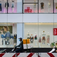 Motorists ride past a Uniqlo clothing store in Hanoi. Japan's Fast Retailing, which owns the Uniqlo brand, also blamed the situation in Vietnam for hold-ups on sweaters, sweatpants, hoodies and dresses   AFP-JIJI