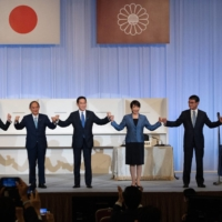 Newly elected Liberal Democratic Party President Fumio Kishida (center) celebrates his win with outgoing Prime Minister Yoshihide Suga (second from left) and fellow candidates on Wednesday in Tokyo. | POOL / VIA AFP-JIJI
