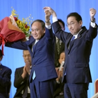 Newly elected Liberal Democratic Party leader Fumio Kishida celebrates his win alongside outgoing Prime Minister Yoshihide Suga on Wednesday in Tokyo. | KYODO