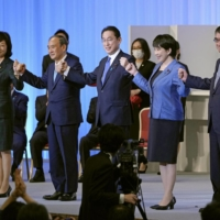 Newly elected Liberal Democratic Party President Fumio Kishida (center) celebrates his win with outgoing Prime Minister Yoshihide Suga and fellow candidates on Wednesday in Tokyo. | KYODO