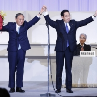 Fumio Kishida joins hands on stage with outgoing Prime Minister Yoshihide Suga after winning the ruling Liberal Democratic Party's leadership election on Wednesday in Tokyo.    BLOOMBERG