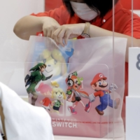 A store attendant puts a box of Nintendo Co. Switch game console in a shopping bag at the company's Nintendo TOKYO store. | BLOOMBERG