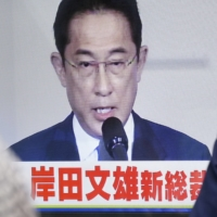 People watch a broadcast of Fumio Kishida speaking as the Liberal Democratic Party's new leader in Tokyo on Wednesday. | KYODO