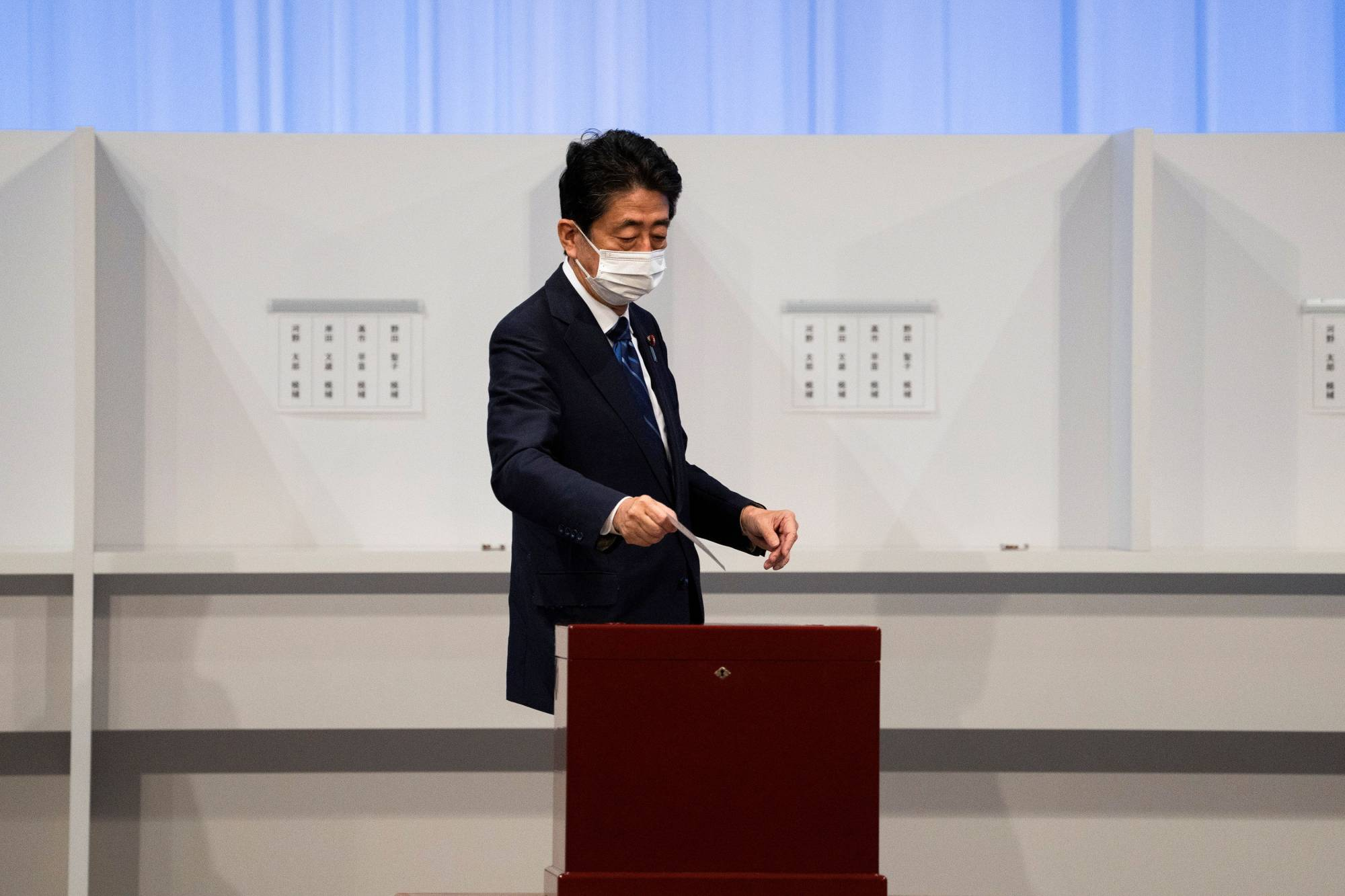Former Prime Minister Shinzo Abe casts his vote in the Liberal Democratic Party's leadership election in Tokyo on Wednesday. | POOL / VIA REUTERS