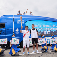Torchbearer Akihito Tanaka (from the visually impaired soccer team) and the 2020 NTT trailer display messages of encouragement for torchbearers.   NTT