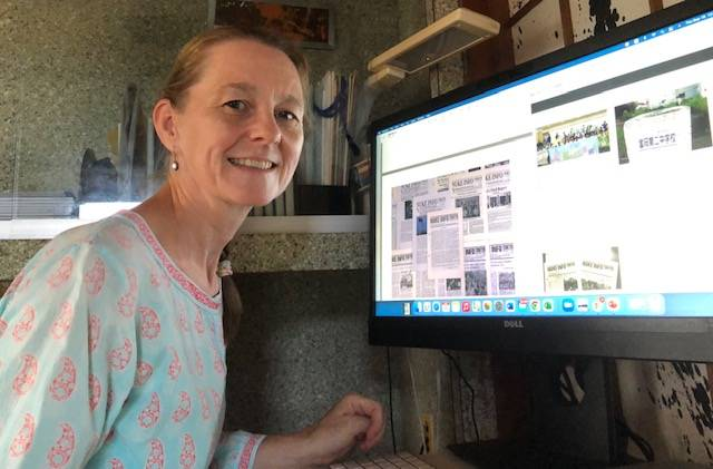 Caitlin Stronell, editor of Nuke Info Tokyo, sits in front of a screen showing past issues of the publication in September. | CITIZENS' NUCLEAR INFORMATION CENTER / VIA KYODO