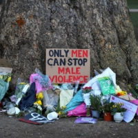 Signs and flowers are left under a tree near the Clapham Common Bandstand in London on March 17, following the kidnap and murder of Sarah Everard. | REUTERS