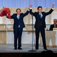 Fumio Kishida (right) celebrates with outgoing Prime Minister Yoshihide Suga after being announced the winner of the Liberal Democrat Party leadership election in Tokyo on Wednesday.    POOL / VIA REUTERS