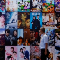 People walk past Chinese movie posters at the 2021 China International Fair for Trade in Services (CIFTIS) in Beijing. Hollywood is struggling to expand its audience in the country, which is now the world's largest movie market. | REUTERS