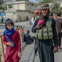 A Taliban fighter poses for a picture holding a flower before offering prayers in Kabul on Friday.   AFP-JIJI