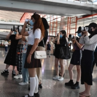 Fans holding cameras wait for celebrities at Beijing Capital International Airport in August.   AFP-JIJI