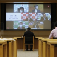 Members of the National Governors' Association are seen on a screen in Tokyo during an online meeting Saturday.   KYODO