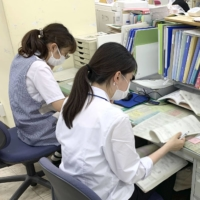Staff at a public health center in Nagoya's Meito Ward make calls to check up on the health of infected individuals on Sept. 16.   KYODO