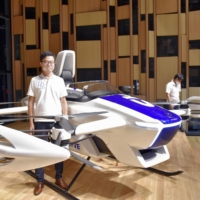 Tomohiro Fukuzawa, CEO of SkyDrive Inc., stands in front of an SD-03 prototype flying car developed by his company, in Tokyo on Aug. 28, 2020.  | KYODO