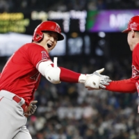 Shohei Ohtani celebrates with the Angels third base coach after hitting a home run against the Mariners in the first inning in Seattle on Sunday.   KYODO