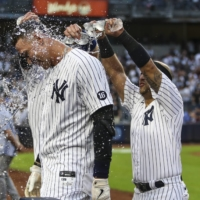 Yankees right fielder Aaron Judge is doused with water after a hitting a walk-off single against the Rays to clinch a wild card spot in New York on Sunday.  | USA TODAY / VIA REUTERS