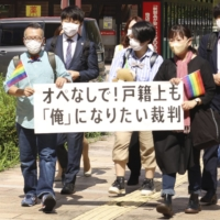 Gen Suzuki (front left) and his supporters walk to the Shizuoka Family Court's Hamamatsu branch Monday. | KYODO