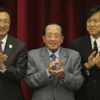 Then-Deputy Foreign Minister Tsuyoshi Yamaguchi (right) claps with China's foreign minister at the time, Yang Jiechi (left), and Cambodia's top diplomat, Hor Namhong, during an Association of Southeast Asian Nations foreign minister's meeting in Phnom Penh in July 2012. | REUTERS