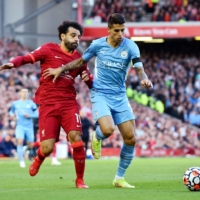 Manchester City's Joao Cancelo (right) and Liverpool's Mohamed Salah vie for the ball during their Premier League match in Liverpool, England, on Sunday.   REUTERS