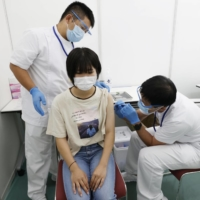 A woman receives a COVID-19 vaccine at a mass vaccination center in Osaka on Sept. 26. | KYODO
