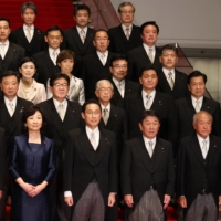 New Prime Minister Fumio Kishida (center front) poses for a group photograph with members of his Cabinet at the Prime Minister's Office in Tokyo on Monday. | BLOOMBERG