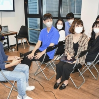 Students, including Yoshiki Goya (far left) and Shin Yoon-cheol (second from left), who participated in the Korea-Japan Exchange Share House program, gather to talk with their housemates in August. | KYODO