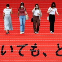 Women wearing protective masks walk on stairs bearing a slogan cheering the Japanese team during the Tokyo 2020 Olympics in the Japanese capital in August. | REUTERS