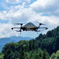 Aeronext Inc.'s drone flies over the mountains around Kosuge Village in Yamanashi Prefecture. The company hopes drone deliveries will solve the last-mile logistical conundrum many rural communities in Japan are facing. | COURTESY OF AERONEXT INC.