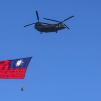 A Taiwan flag is carried across the sky during a national day rehearsal in Taipei on Tuesday.    REUTERS