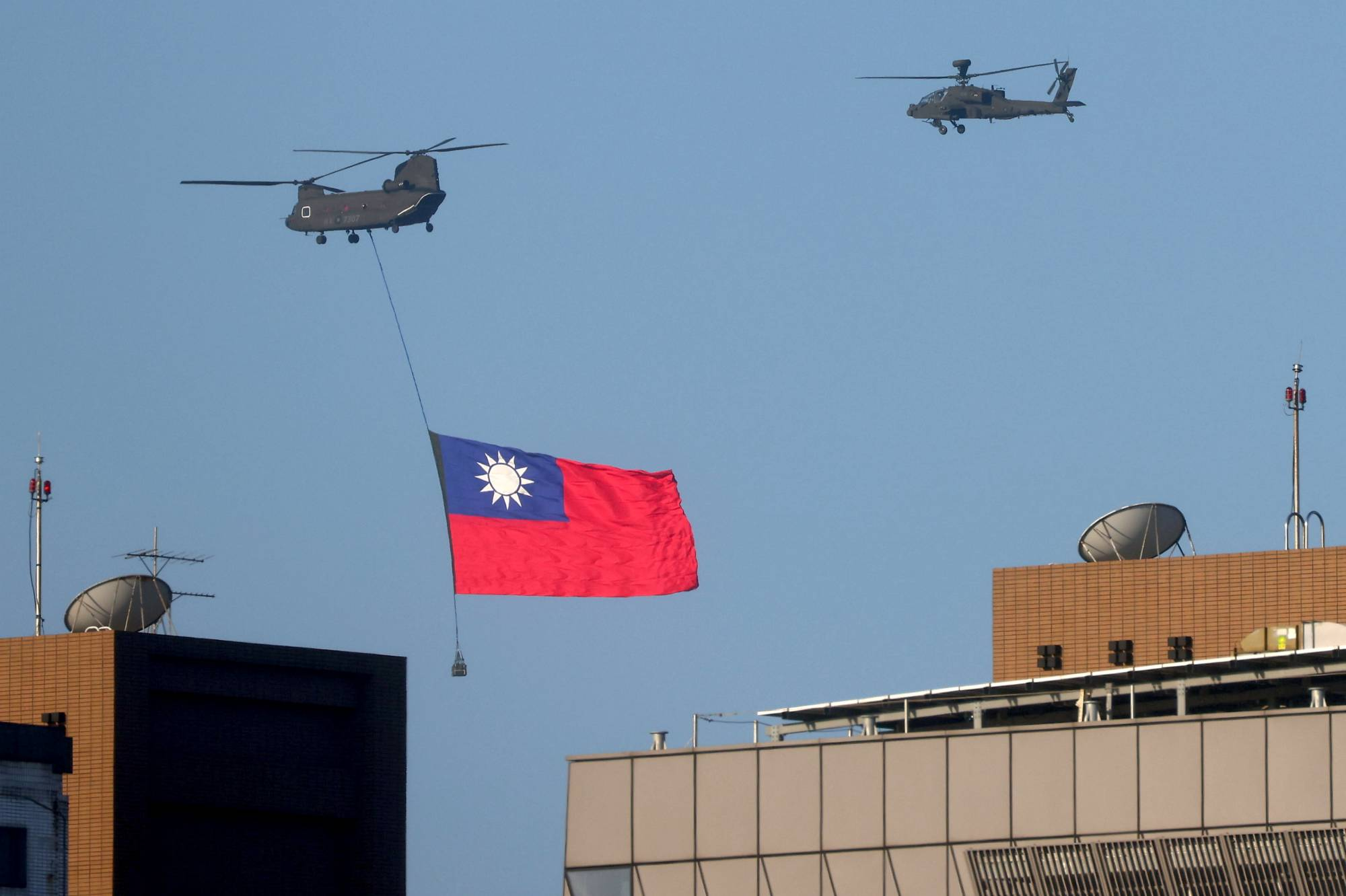 A Taiwan flag is carried above Taipei during a National Day rehearsal on Tuesday. | REUTERS