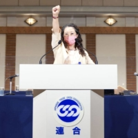 Tomoko Yoshino calls for unity from the stage after she is elected as the first female chief of Japan's largest labor organization, Rengo, at a regular convention in Tokyo on Wednesday.  | RENGO / VIA KYODO