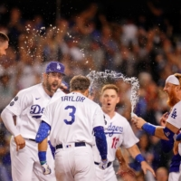 The Dodgers celebrate at home plate after Chris Taylor's game-winning home run against the Cardinals in Los Angeles on Wednesday. | USA TODAY / VIA REUTERS