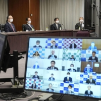 Bank of Japan Gov. Haruhiko Kuroda (left) attends a videoconference of the central bank's branch managers Thursday. | KYODO