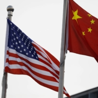 Chinese and U.S. flags flutter outside the building of an American company in Beijing. | REUTERS