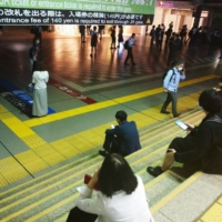 Passengers wait at Shinagawa Station in Tokyo after trains were suspended on Thursday. | KYODO