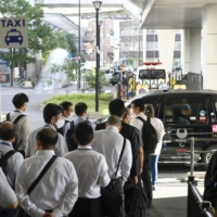 People line up for a taxi outside Nippori Station in Tokyo on Friday morning as services of Nippori Toneri Liner trains were still suspended. | KYODO