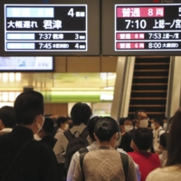 A signboard shows long delays in train services at Chiba Station on Friday. | KYODO