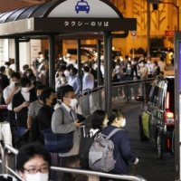 Many people wait for a taxi outside Shinagawa Station in Tokyo in the early hours of Friday following a strong quake late Thursday. | KYODO