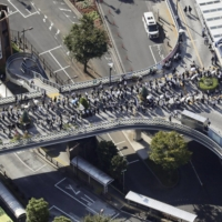 A crowd spills out of Kawaguchi Station in Saitama Prefecture on Friday morning. | KYODO