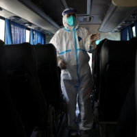 A driver makes checks on a bus before departing from a quarantine hotel for travelers entering China in Dalian, Liaoning province, on Sept. 29.   REUTERS