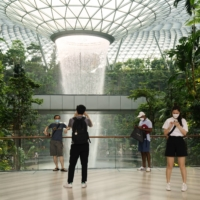 Visitors take photographs in front of the Rain Vortex indoor waterfall feature at the Jewel Changi Airport mall in Singapore. Singapore Trade Minister Gan Kim Yong said the government is committed to reopening the country gradually after reimposing domestic curbs such as making work-from-home the default and cutting the number of diners to deal with a surge in cases.  | BLOOMBERG