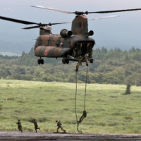 Ground Self-Defense Force soldiers rappel from a CH-47 Chinook helicopter during an annual training session near Mount Fuji at Higashifuji training field in Gotemba, Shizuoka Prefecture, in August 2019. | REUTERS