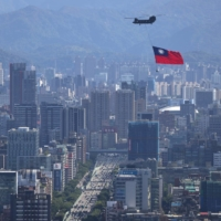 A Taiwan flag is carried by a Chinook helicopter during a rehearsal for the upcoming National Day celebration in Taipei on Thursday.  | REUTERS