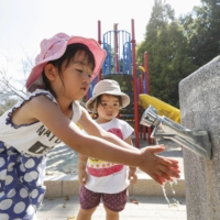 Children wash their hands at a park in Wakayama after water services were restored following a six day outage.  | KYODO