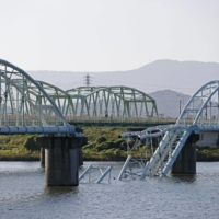 The collapse of an over 500-meter-long bridge that spans the Kinokawa river in Wakayama caused two water pipes to fall into the river on Sunday. | KYODO