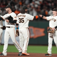 San Francisco Giants right fielder Mike Yastrzemski (5) and shortstop Brandon Crawford (35) celebrate with teammates after defeating the Los Angeles Dodgers in Game One of the NLDS on Friday.  | USA TODAY / VIA REUTERS