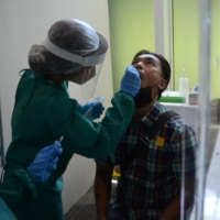 A health worker takes a swab during a simulation of COVID-19 health protocols in Bali on Saturday.    AFP-JIJI